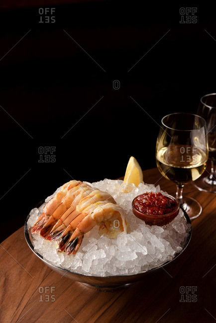 Shrimp cocktail on ice served with cocktail sauce beside white wine with copy space
