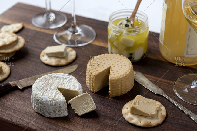 Plant based, dairy free cheeses on wooden board with crackers and wine