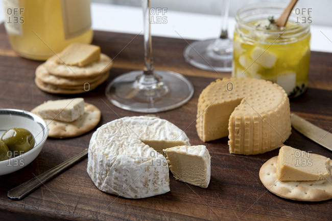 Close up of plant based, dairy free cheeses on wooden board with crackers and olives