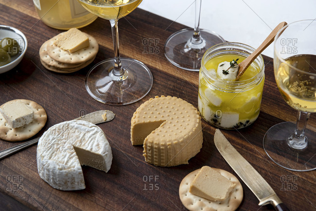 Top view of plant based, dairy free cheeses on wooden board served with wine and crackers