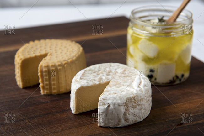 Three plant based, dairy free cheeses on wooden board