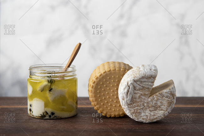 Plant based, dairy free cheeses on wooden board with white marble background