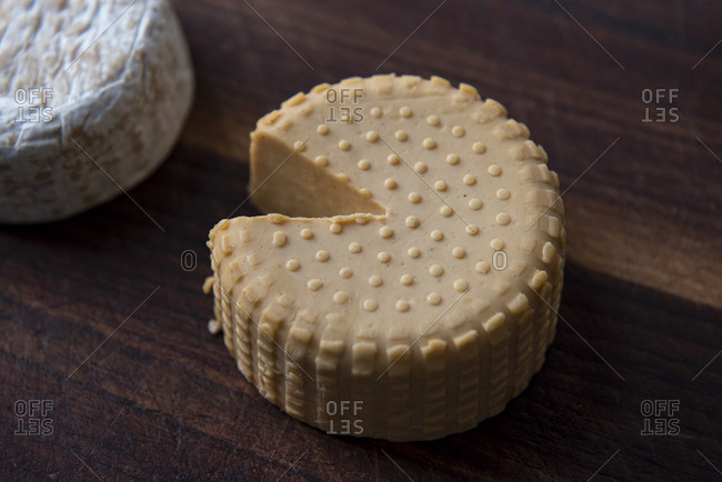 Top view of two plant based, dairy free cheeses on wooden board