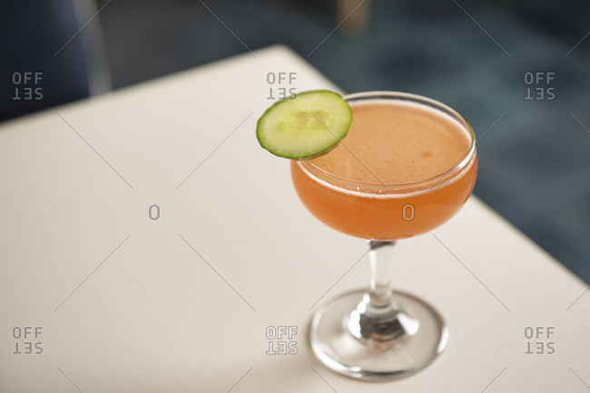 Pink cocktail in coupe glass with cucumber garnish