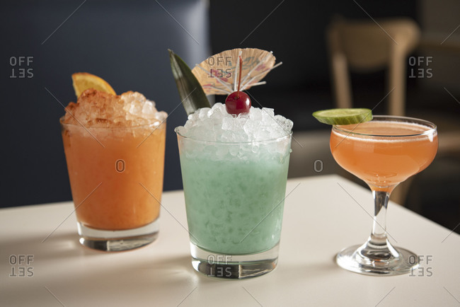 Three tiki cocktails served on a white table