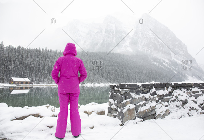 Tourist in pink snow suit enjoying the chill view at Lake Louise, Alberta, Canada