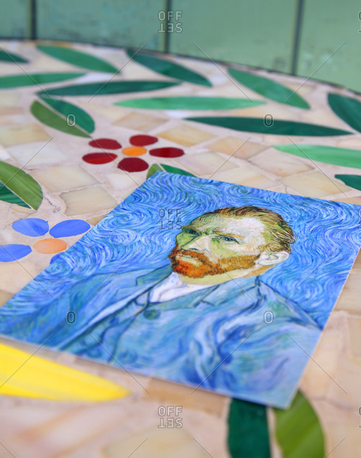 Arles, France - January 23, 2010: A postcard of the Vincent Van Gogh self portrait on colorful cafe table outdoors