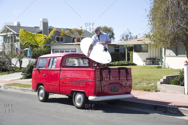 Santa Monica, California - February 3, 2016: Middle aged man loading surfboard in back of red vintage pickup truck in a residential neighborhood