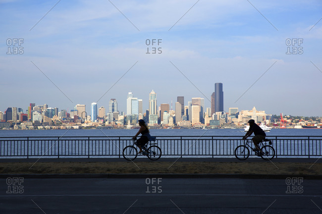 Seattle, Washington - August 3, 2015: View of Seattle skyline with silhouette of a couple riding bicycles in the foreground