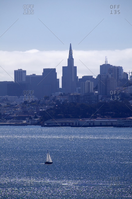 A sailboat seen in the San Francisco Bay with buildings in the background, California