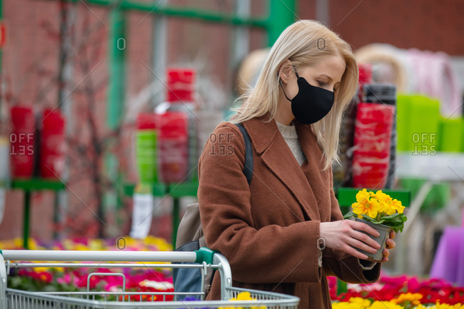 Blonde woman in face mask and coat chooses yellow flowers in a garden store