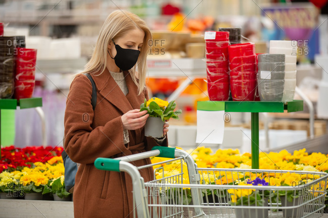 Blonde woman in face mask and coat chooses flowers in a garden store