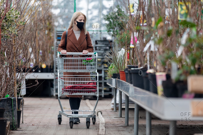 Blonde woman in face mask and coat looks at trees in a garden store