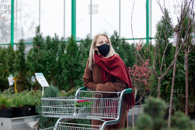 Blonde woman in face mask and coat shopping in a garden store