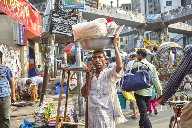 Dhaka, Bangladesh - April 27, 2013: A man with a bowl filled with goods to sell on his head walking on a very busy street