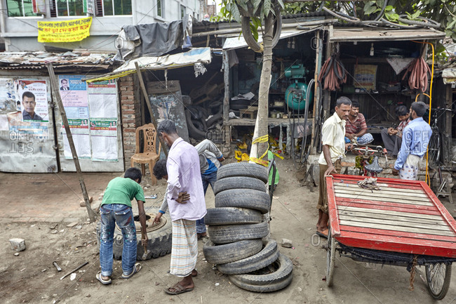 Dhaka, Bangladesh - April 26, 2013: Group of men repairing rickshaws in a workshop in Dhaka