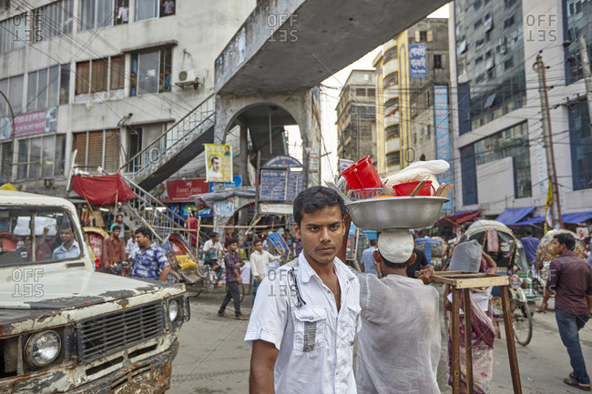 Dhaka, Bangladesh - April 27, 2013: A young man posing for a photo on a very busy market street in Dhaka, Bangladesh