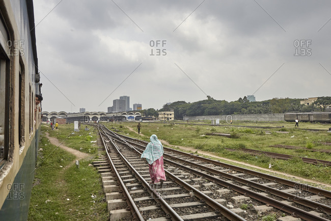 Dhaka, Bangladesh - April 28, 2013: A woman walking on the tracks near the Kamalapur Railway Station