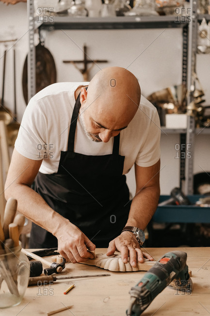Male master in apron using sharp chisel while creating carved ornate decorative wooden detail at workbench with tools in workshop