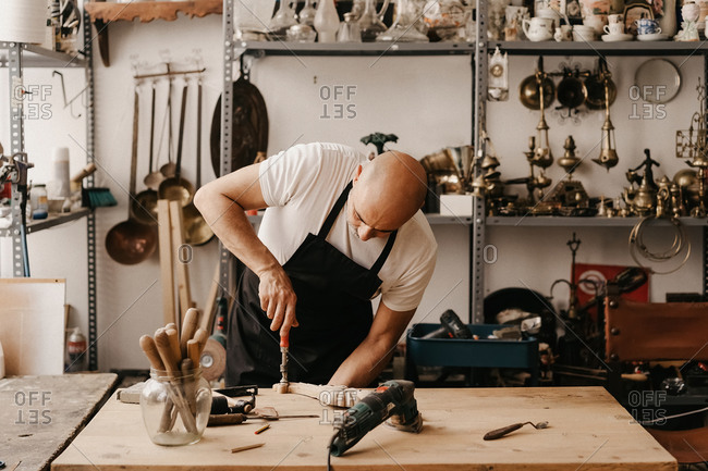 Woodworker in apron carving wood with chisel and hammer while creating ornate detail in workshop