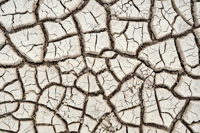 Top view closeup textured background of rough cracked barren waterless soil during drought
