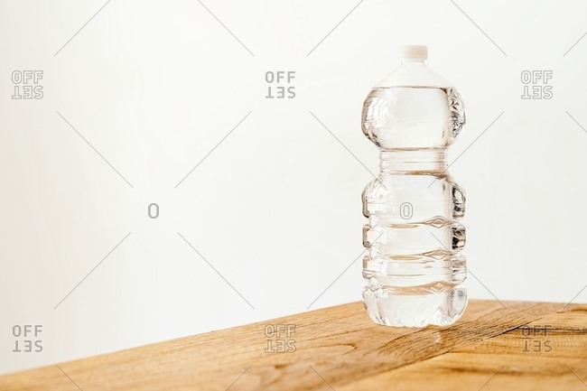Transparent plastic bottle filled with fresh water placed on wooden table against white background