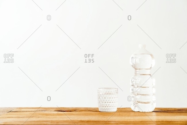 Empty glass and plastic bottle filled with pure fresh water placed on wooden table against white wall