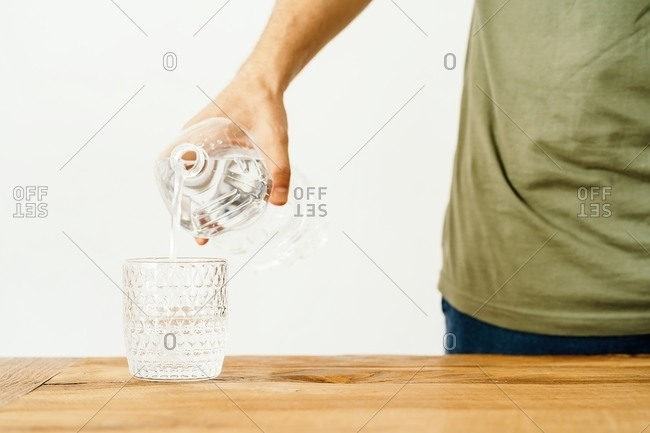 Crop anonymous male filling glass with fresh mineral water from plastic bottle