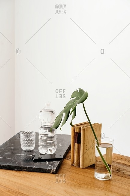 Fresh green monstera stem in vase arranged on wooden table near full bottle of water and glass against white wall in room with minimalist design