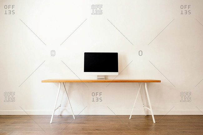 Modern computer placed on wooden table in contemporary light room with minimalist interior