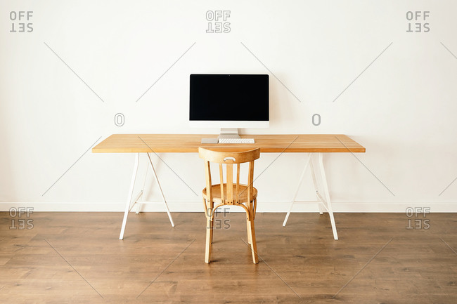 Modern computer placed on wooden table near chair in contemporary light room with minimalist interior
