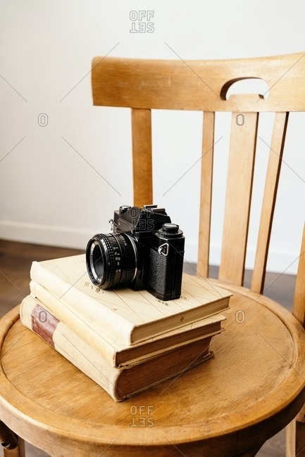 Old fashioned photo camera placed on stack of vintage books on wooden stool in creative workplace