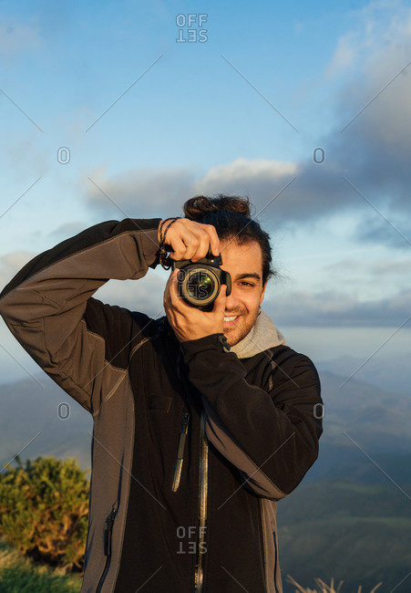 Young male photographer with professional photo camera taking pictures of nature while standing on top of rocky mountain looking at camera