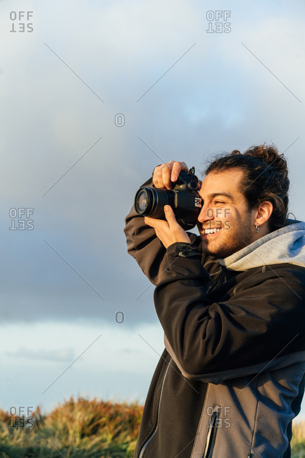 Side view of male photographer with professional photo camera taking pictures of nature while standing on top of rocky mountain