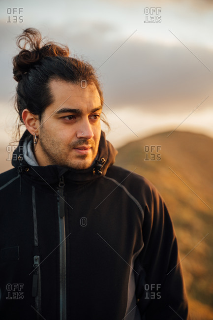 Lonely male explorer with backpack standing on top of green hill and contemplating nature while traveling through mountainous terrain