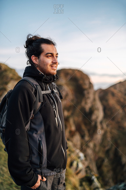 Side view of lonely male explorer with backpack standing on top of green hill and contemplating nature while traveling through mountainous terrain