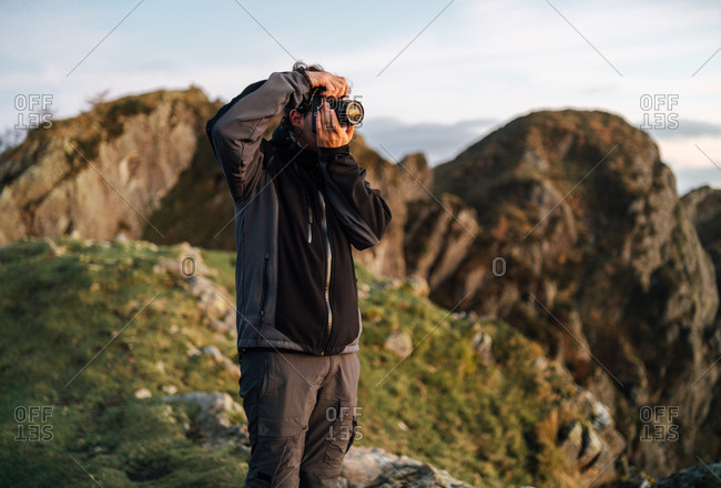 Side view of unrecognizable male photographer with professional photo camera taking pictures of nature while standing on top of rocky mountain