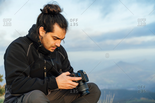 Young bearded male traveler checking pictures on professional photo camera while resting after hiking through highlands in autumn day