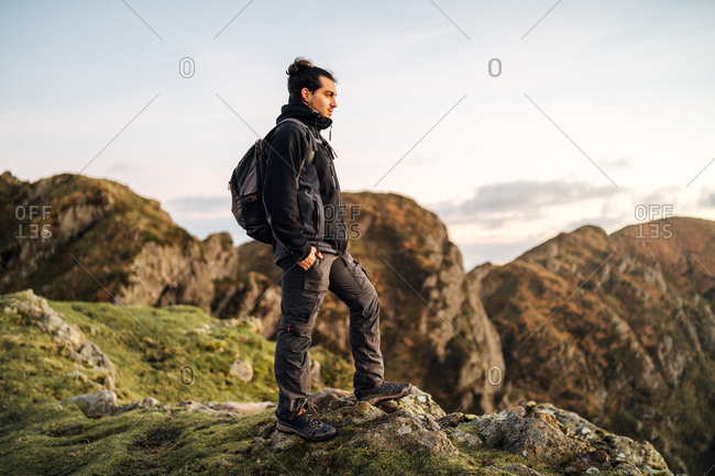Side view of lonely male explorer with backpack standing on top of green hill and contemplating nature while travelling through mountainous terrain