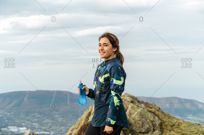 Side view of positive young ethnic female athlete in sportswear smiling and looking at camera while drinking water after workout in mountains