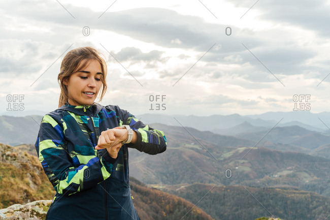 Confident young ethnic sportswoman in activewear checking time on smart watch during outdoor training in mountainous terrain against cloudy sky
