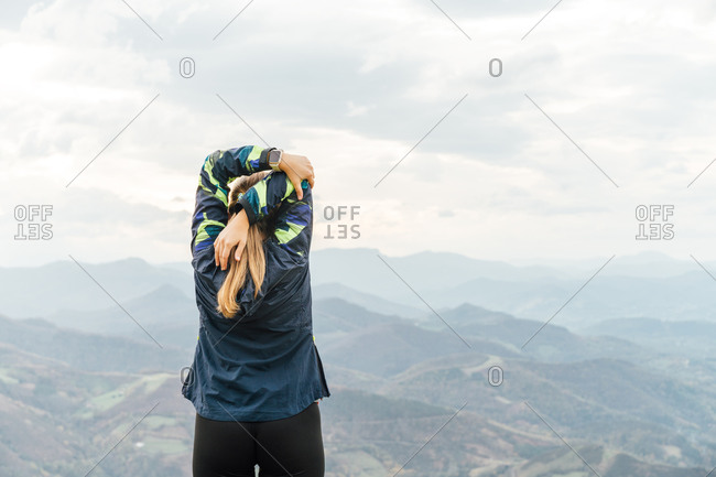Back view of unrecognizable female athlete in sportswear stretching arms after outdoor workout and admiring picturesque mountain view