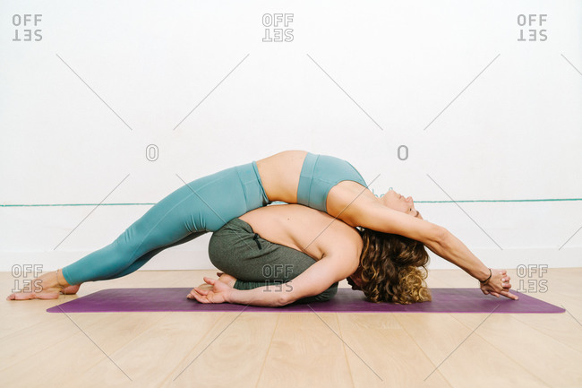 Side view of flexible couple in activewear practicing acroyoga in Balasana and Matsyasana on mat in bright studio