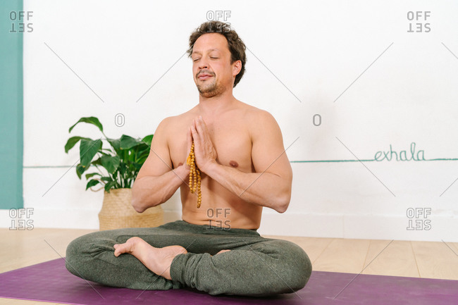 Peaceful male with naked torso sitting with crossed legs and beads in Padmasana and meditating with closed eyes while practicing yoga in studio
