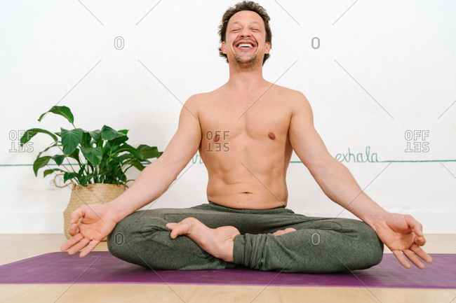 Low angle of shirtless delighted male sitting in Padmasana on mat with mudra hands and practicing yoga with closed eyes