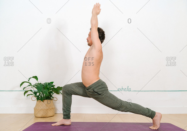 Side view of shirtless male standing barefoot on mat in Anjaneyasana and practicing yoga in bright studio