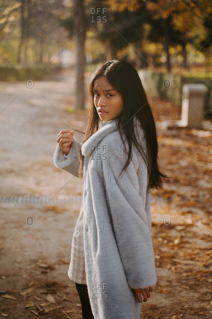 Back view of ethnic female model in coat walking in autumn park while looking over shoulder at camera