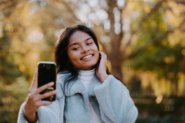 Smiling ethnic female taking self portrait on smartphone while standing in autumn park and smiling