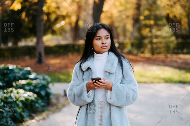 Ethnic female wearing autumn coat walking in park and messaging on social medial with friends via smartphone during stroll on sunny day
