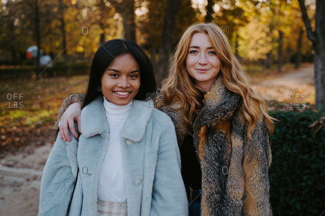 Cheerful multiracial female friends cuddling and looking at camera while standing in autumn park and spending weekend together